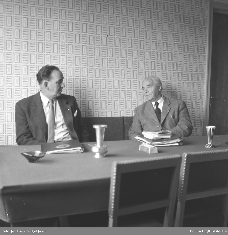 To menn sitter ved et bord. Distriktssjefen i Televerket Sigurd Torgersen til venstre i bildet. Han har en mørk dress med hvit skjorte og slips på seg. Mannen til høyre er også iført dress med hvit skjorte og slips. Det lange bordet har en ganske mørk duk og oppå ligger noen permer og papirer. Der står også et par askebeger og blomstervaser. Veggen bak dem har et firkantmønster og ryggen på noen lenestoler ses i forkant av bildet. En døråpning ses helt til høyre på bildet.