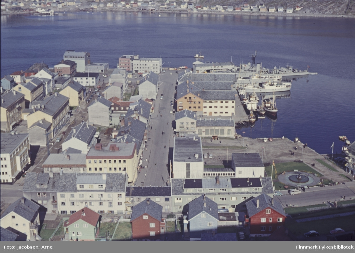 Hammerfest sentrum fotografert fra fjellet Salen. Gaten midt på bildet er sjøgata og gata ovenfor er Storgata. Gata som går på tvers nederst er Strandgata og Salsgata ovenfor den. Helt til høyre ligger Rådhusplassen med rådhusest, fontenen og havneområdet til høyre er Jernteppet, Verftsfjæra og Nissenkaia. Et marinefartøy, fregatten KNM Tromsø, ligger ved Dampskipskaia og en fiskeskøyte er på vei inn til Hammerfest. En del fiskefartøyer ligger ved Nissenkaia. I enden av Sjøgata ligger FFRs adminstrasjonsbygg og ved siden av det til venstre er Nord-Norges Salgslag. Til høyre ligger havnevakta og godsterminalen. Øverst på bildet, på andre siden av bukta er bydelen Fuglenes  med Fuglenesveien som går langs fjellsiden.