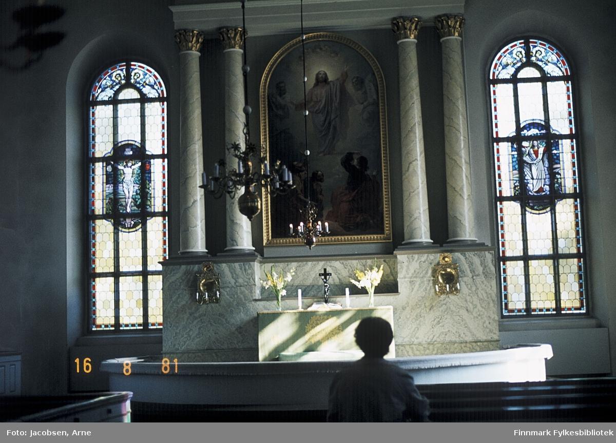Aase Jacobsen på en kirkebenk i Finland. To gotiske vinduer med mosaikkmotiv på begge sidene av alteret. Fire søyler som ser ut til å være av marmor med metalltopper på hver side av et stort bilde med Jesusmotiv. Et lite kors står på alteret sammen med to stearinlys og to figurer. En lysekrone med stearinlys henger ned fra taket. To metallfigurer henger på murveggen som er en del av alteret.