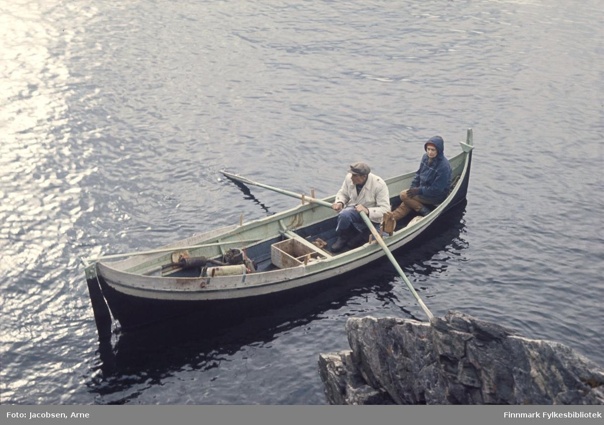 Arne Nakken og Aase Jacobsen på tur i Nordlandsbåt. Han med årene og iført lys jakke, gummistøvler og lue. Aase med mørk jakke, hetten på og hansker. I båten ligger en fiskekasse. Det er stille på sjøen og solskinn.