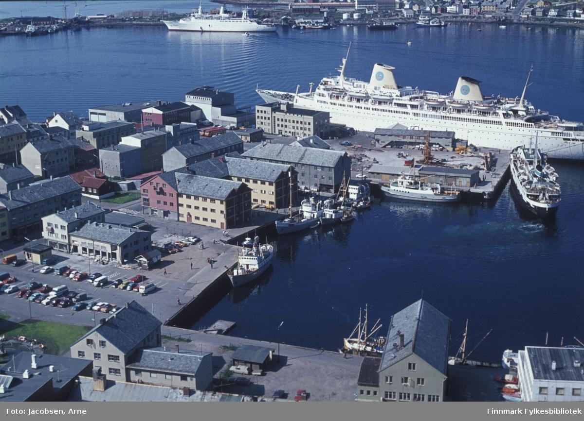 """Hammerfest havn en flott sommerdag i 1966 eller 1967. Nede til venstre ser man Rådhusplassen med en del biler parkert. Bygget nederst med røstet mot kamera er Finnmarksbo. Nissengården og Televerksbygget, nå biblioteket sees midt i bildet. Et skip ligger ved Bangkaia og ved Rådhuskaia ligger FFR-båten """"Tamsøy"""". Ved Nissenkaia ligger en liten klynge båter. Ved godsterminalen ligger FFR-båten """"Rypøy"""" ikke langt fra  Hurtigruta """"Lofoten"""". Ved Dampskipskaia/Hurtigrutekaia ligger et turistskip, SAL`s """"Kungsholm"""". Foran baugen ligger FFR´s hovedadministrasjon og Nord-Norges Salgslag. På andre siden av havna ligger bydelen Fuglenes. Turistskipet er er det Franske M/S Renaissance som ble levert til rederiet i mai 1966. Hvis bilde er datert 1966 så ligger det to splitter nye skip her da M/S Kungsholm hadde sin jomfrutur i april 1966. Noen småbåter er ute på havna og Hammerfest videregående skole ses øverst bak hekken på turistskipet."""