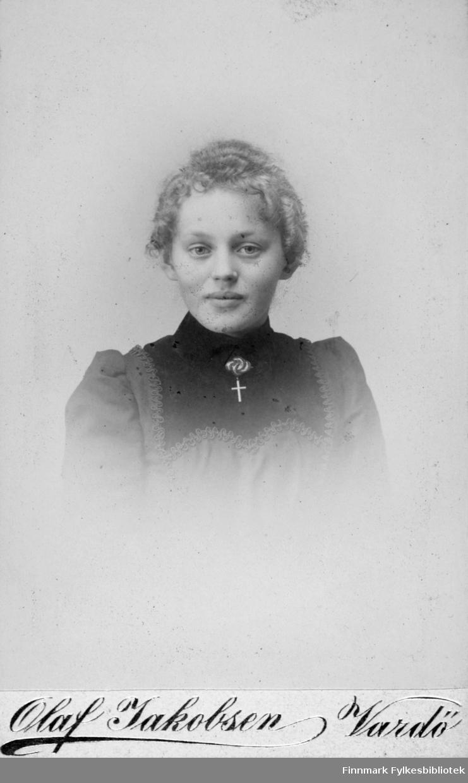 Portrett av Aagot Jacobsen. Hun arbeidet som fotograf i Vardø. Hun brukte sin brors, Olaf Jacobsen, fotograflogo, og gikk antakelig i lære hos han. På bildet er hun kledt i mørk kjole eller bluse med innfelt liv, pyntet med bånd. I halsen har hun en brosje og et smykke med korsanheng