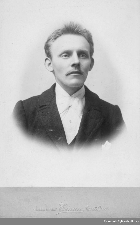 Portrett av ung ukjent mann. Han er kledt i mørk jakke, hvit skjorte og med en lys sløyfe