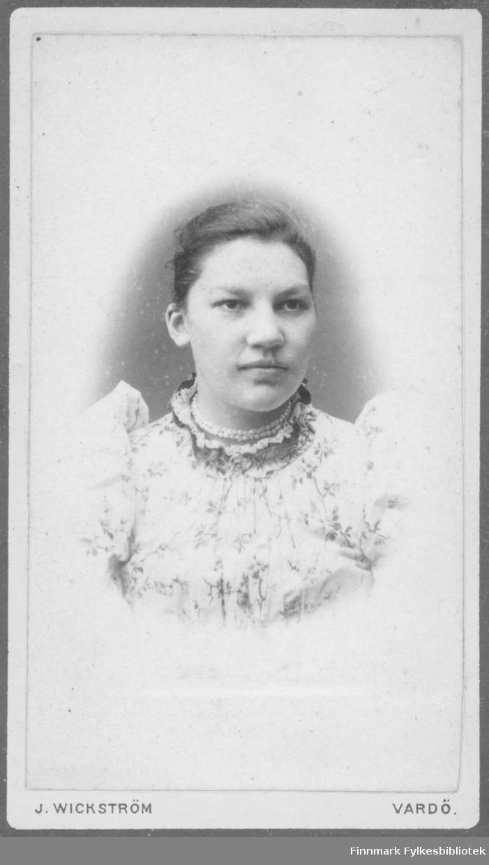 Portrett av ukjent kvinne. Hun har på seg en lys kjole eller bluse med blomstermønster og store puffermer. I halsen har hun et dobbelt perlekjede