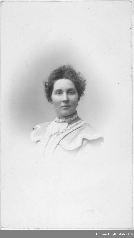 Portrett av en kvinne som muligens er Dagny Isaksen fra Senja, i følge familien. Hun er kledt i en lys jakke eller bluse som er pyntet med sløyfe, og bånd av blonder