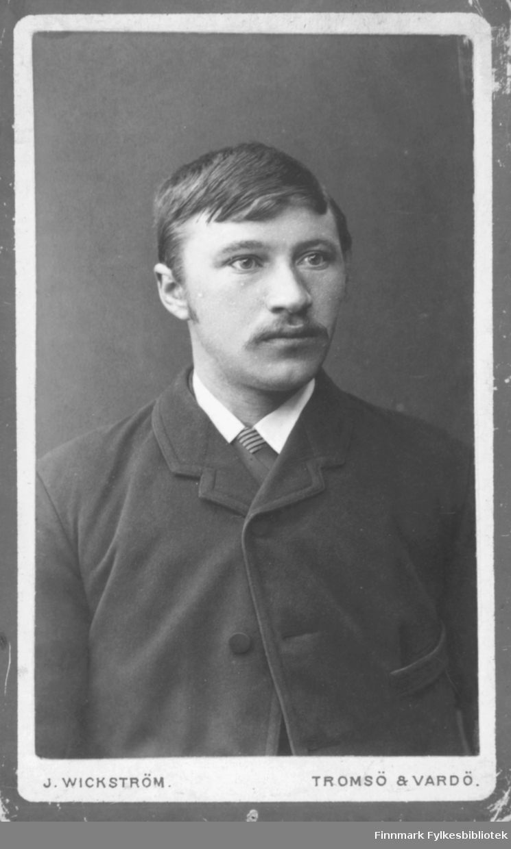 Portrett av ukjent mann med bart. Han er kledt i mørk jakke og hvit skjorte