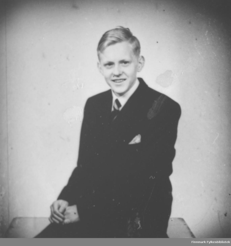 Portrett av Per Jacobsen f. 1932 i Bergen. Han er sønn av August Magnus Jacobsen, og sønnesønn til smedmester i Vardø Ole Sigfrid og hustru Anna Vibe Jacobsen. På bildet er han kledt i mørk jakke og bukser. Hvit skjorte og slips. I brystlommen har han et lyst tørkle