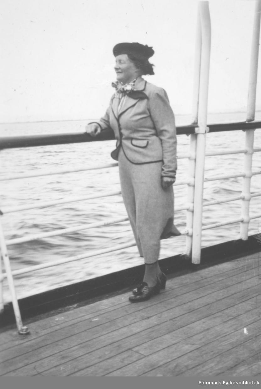 Bilde av lærerinne Julie Jacobsen fra Vardø på hurtigruten. Hun står ved rekken og ser ut over sjøen. Hun er kledt i en lys drakt, mørk lue og halstørkle. På føttene har hun lave snøresko