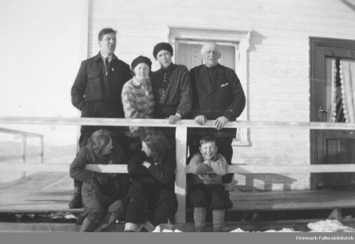 Fotografi av fem ukjente personer. To menn, fire kvinner og en gutt. De er på en veranda. To av kvinnene og gutten sitter og holder rundt gelenderet. De andre står bak dem. Verandaen er rundt et hvitt trehus. Døren har glassvindu med gardiner. Vinduet har utskjæringer på de hvite listene. Personene er kledt i turklær