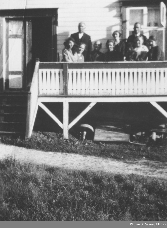 Fotografi av en gruppe ukjente personer. De sitter på en veranda utenfor et hvitt trehus. Det er utskæringer på gelenderet. Det går en trapp opp til en bred døråpning med to dører inn til huset. Den ene står åpen. Vinduet som er bak menneskene har fire glassruter. Det ene er åpent. Det står to menn på verandaen. Resten er seks kvinner og ei jente