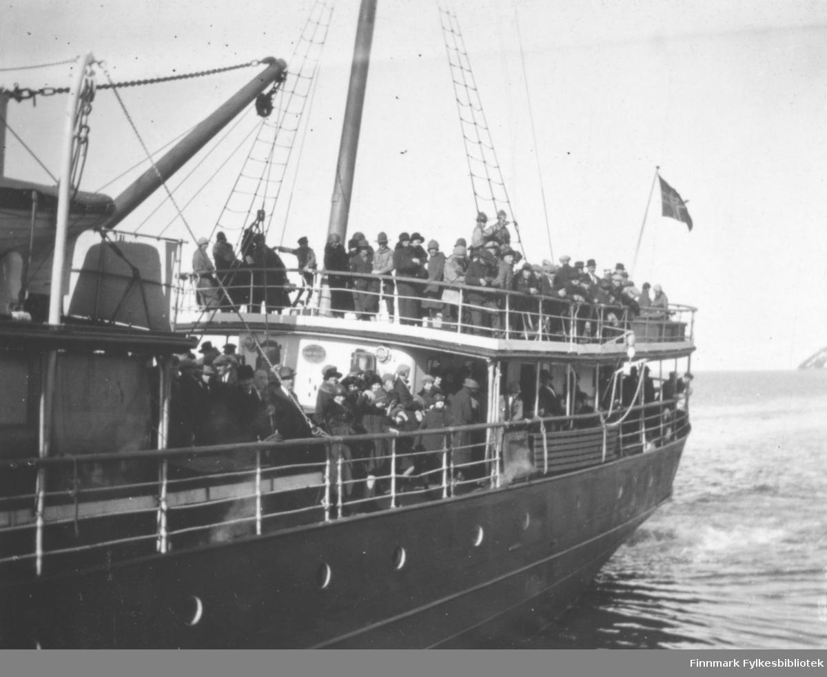 Fotografiet viser sannsynligvis av et av de mange hurtigruteskipene som fraktet evakuerte Finnmarkinger hjem i perioden 1945-46. Båten er overfylt av kvinner, menn og barn. Det norske flagget vaier i akterenden av båten.