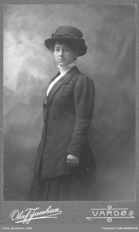 Portrett av en ukjent kvinne tatt i et fotoatelier. Hun er kledt i en lang jakke pyntet med knapper, og et skjørt. Hun har også en høyhalset hvit bluse på seg. På hodet har hun en hatt