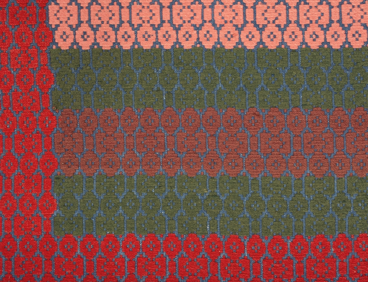 """Täcke vävt i opphämta. Ytmönster av små """"ringar"""" och rektanglar. En mönsterrapport är ca 45 mm på höjden. Blå tuskaftsbotten i linne. Mittspegeln är randig i grönt, rödbrunt, grönt, rosa, som därefter upprepas, varje rand är 65-70 mm bred. Röd bård runt om, ca 140 mm bred. Täcket är ihopsytt på mitten av två delar. Mittsömmen är sydd med efterstygn i dubbel lintråd.Varp i indigoblått 1-trådigt z-spunnet lingarn, 17 trådar/cm.Botteninslag samma som varpgarnet, 12 inslag/cm.Mönsterinslag i 2-trådigt z-tvinnat ullgarn, 11 inslag/cm.Täcket är märkt på baksidan med en påsydd tyglapp med texten: """"VÄVT AV ELNA OLSDOTTER F. 1828, S. WALLÖSA, SJÖRUP SN. TROL. VID HENNES GM. C:A 1850. GÅVA 1965 FRÅN: MARTIN OCH EMMA HANSSON LJUNITS HÄRAD""""."""