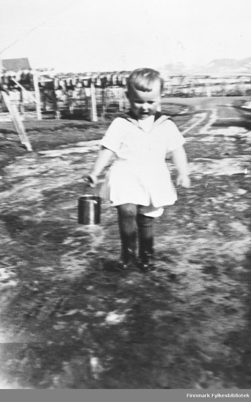 Margrethe Dyrseth med matroskjole og spann i hånda. I bakgrunnen fiskehjeller og huset til Hermann Dahl.