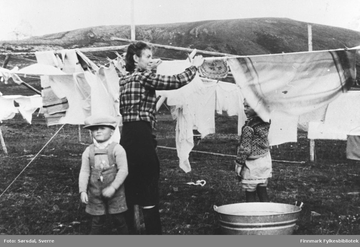 Else Sørsdal henger klær til tørk mens familien bodde i Syltefjord. Else var gift med overlegen på Vardø sykehus, Sverre Sørsdal. Sykehuset ble bombet og brant ned til grunnen 1. mars 1942. Etter noen urolige måneder ble det avgjort å flytte til Syltefjord, hvor internatet ble tatt i bruk som provisorisk sykehus. Barna på bildet er Randi og Eirik Sørsdal