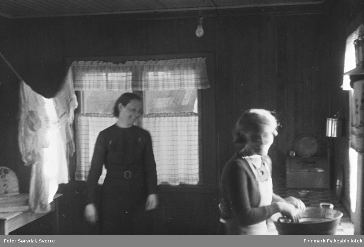 Else Sørsdal og hushjelp på kjøkkenet i Vardø 1936. Det henger gardiner i vinduene og klær til tørk på snor. Hushjelpen vasker kopper i en balje.