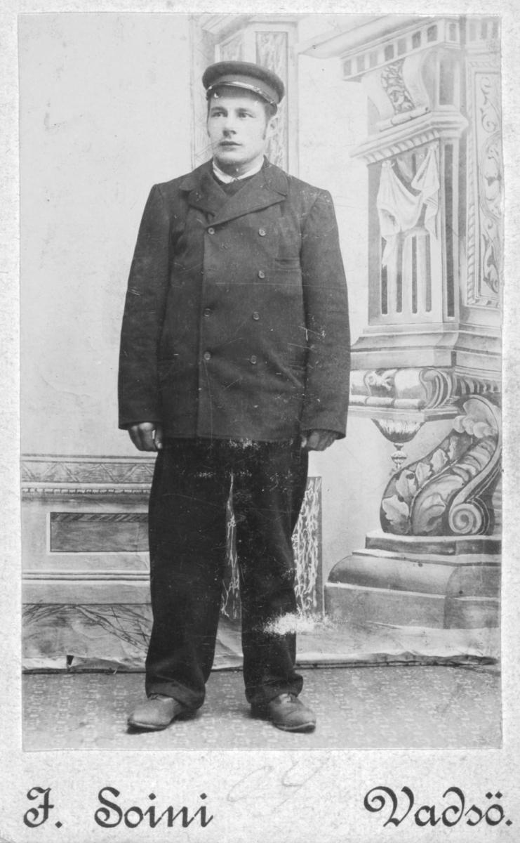 Et portrett av en ung Werner Alfred Korbi. Han er kledd i jakke, skjorte, bukser, hansker, sko og hatt. I bakgrunnen kan man se en malt kulisse.