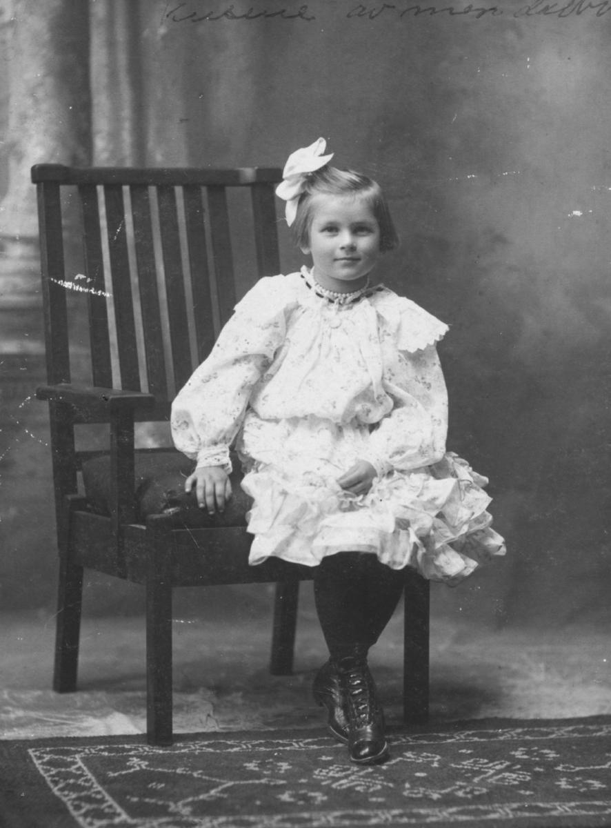 Et portrett av en liten pike. Hun er kledd i en vakker kjole og har på seg strømper og sko. I håret har hun en hårsløyfe og et perlesmykke rundt halsen. Hun sitter på en stol. På gulvet foran henne kan man se en matte.  Bildet trolig tatt på begynnelsen av 1900-tallet.