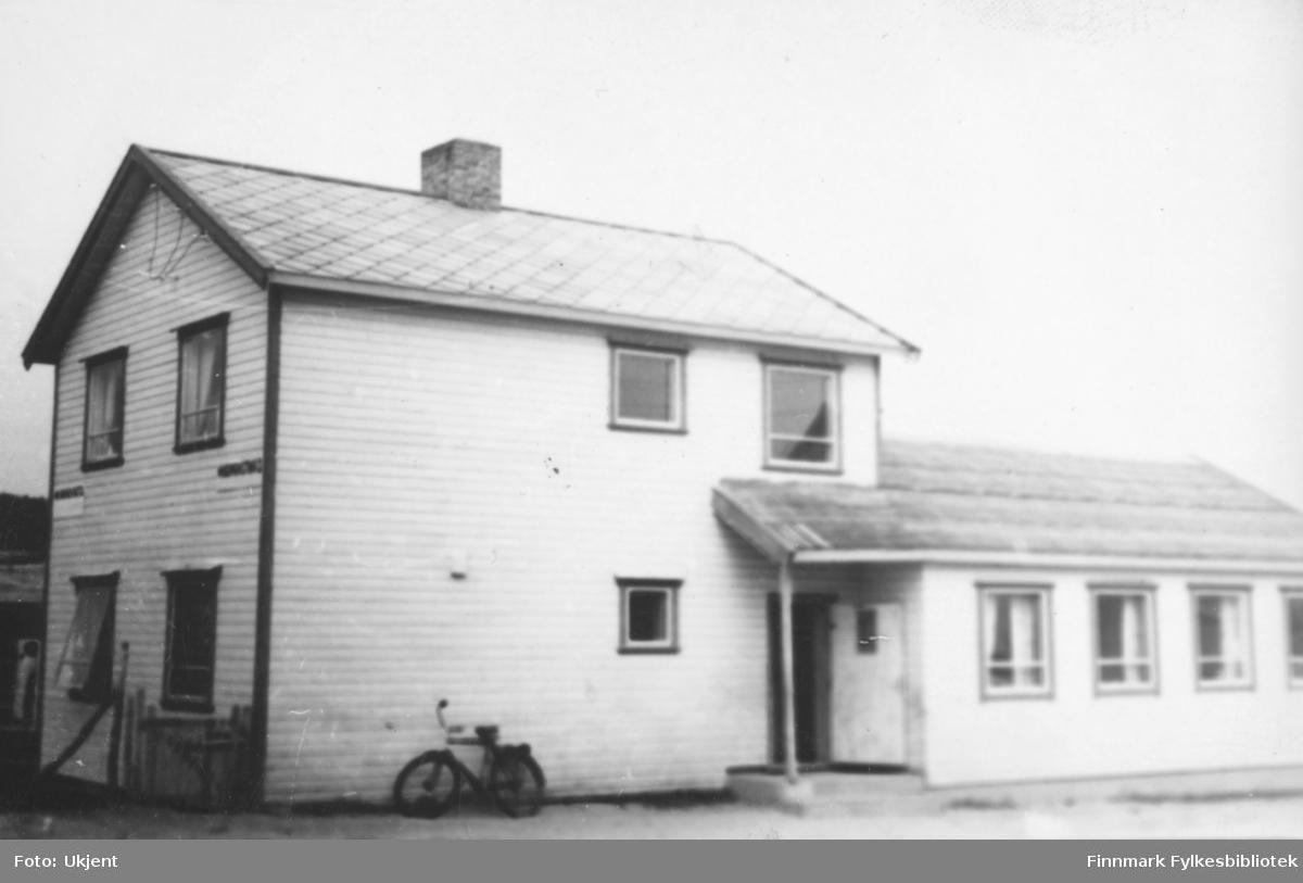 Kautokeino husmorslag, bildet tatt på 1950-tallet. På huset kan man se en dør, trolig inngangen. Huset har også mange vinduer med gardiner i. På taket kan man se en skorstein. Mot veggen lener det seg en sykkel. Ved siden av huset kan man se en strømlinje.