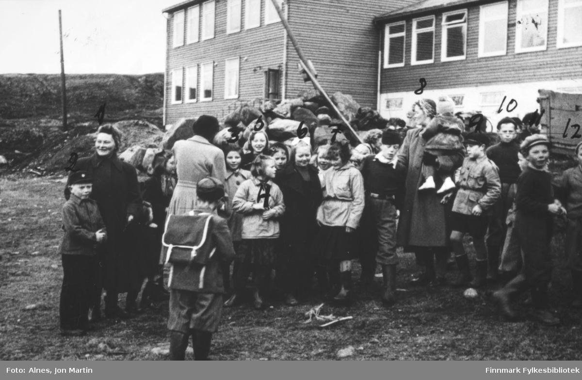 Skolestart i Øksfjord høsten 1953, og den helt splitternye barneskolen skal tas i bruk. Elevene og noen foreldre samlet utenfor skolebygningen