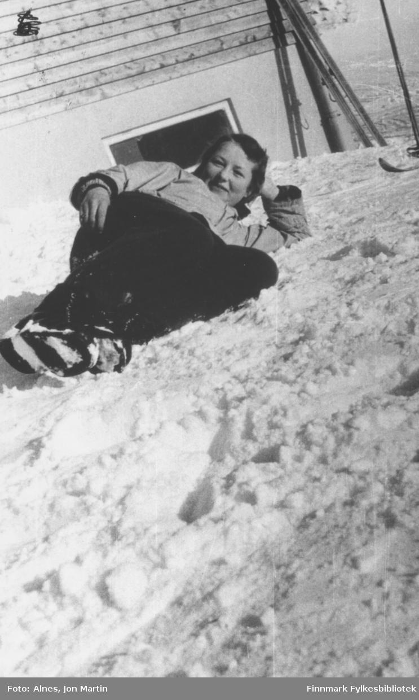 Nan Kiil i påskesola utenfor den nye barneskolen i Øksfjord, vinteren 1953. Bildet er nok tatt etter en skitur, for skiene står stilt opp mot skoleveggen i bakgrunnen