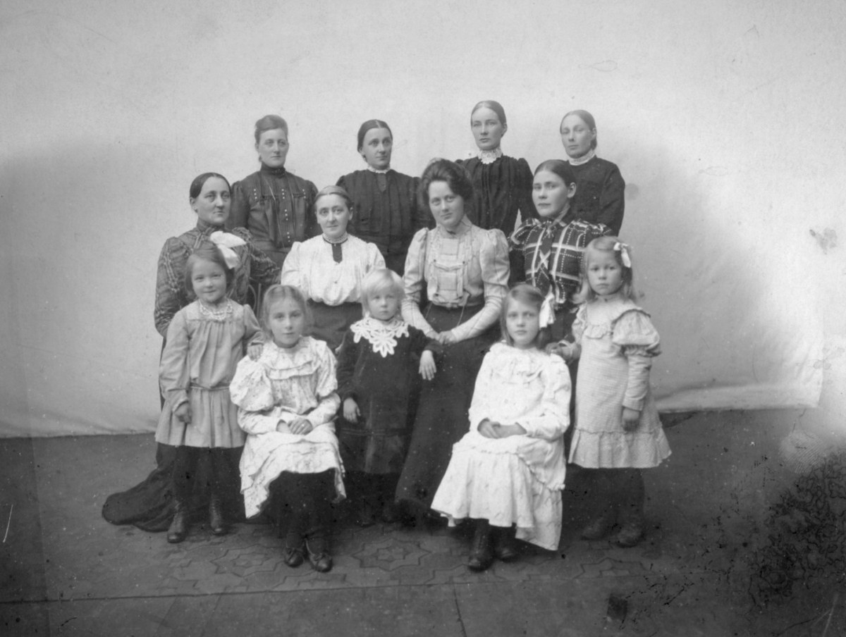 Et gruppeportrett av flere kvinner og små jenter. Olga Marie Pedersen sitter som nummer tre f.v. i andre rad. De andre er ikke identifisert. Kvinnene er kledd i kjoler, enkelte av dem har på seg smykker. De små pikene er også kledd i kjoler, enkelte av dem har sløyfer i håret. Jenta som er nr. en f.v. første rad har et perlesmykke rundt halsen.