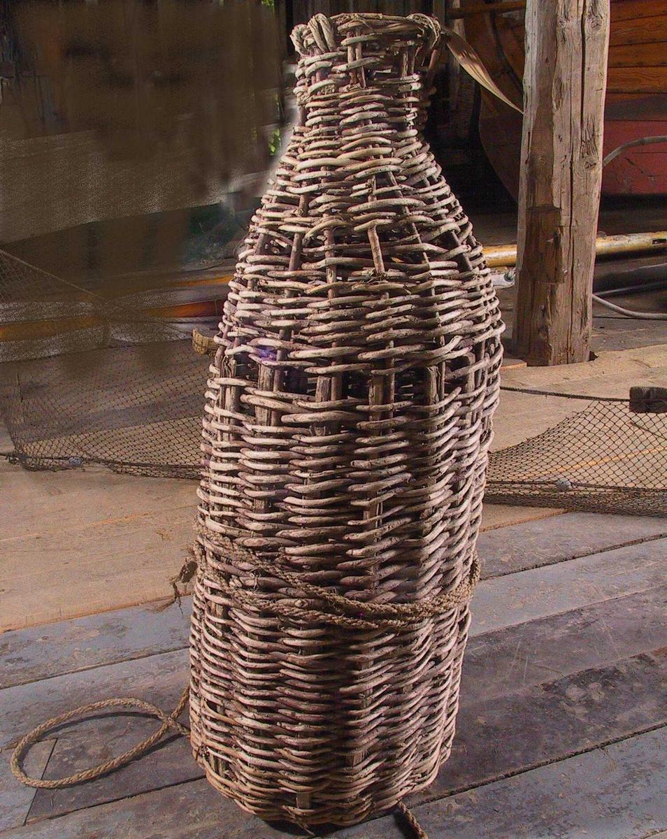 """Åleteine, kurvflettet arbeid  Flaskeformet.  Ruse eller teine   flettet  av   pilekvister,   til ålefiske på sjøbunnen.  Brukt av siste eier fisker Nils Terjesen, Homborsund, til sin død  1967. alder uviss, meget gamle og av gammel type.    Tilst. 1968: Noe løs grunnet tørke, et par mindre hull i  fletningen,  spesielt på """"skuldrene"""".   Grastau  knyttet fast til nedre del."""