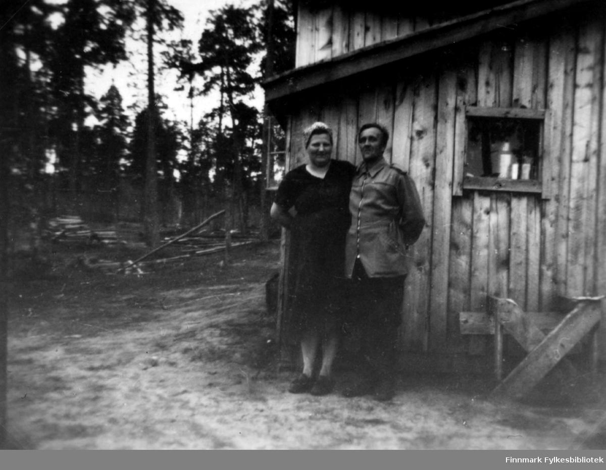 """Fotografi av Hilma og Kiril Ananin som står utenfor en trebygning. I bakgrunnen er det skog med høye trær. På bakken ligger felte trær. Hilma er kledt i en mørk kjole og et tørkle på hodet. Kiril er kledt i skjorte og mørk bukse. Bildet har teksten """"Talvi tupa"""" som betyr """"vinterhytte""""."""
