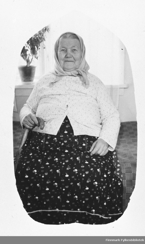 Portrett fra Amanda Mikkelsdatter, g. Reisænen. Hun sitter innendørs ved vinduet med mørk blomstrete kjole og lyst tørkle på seg.