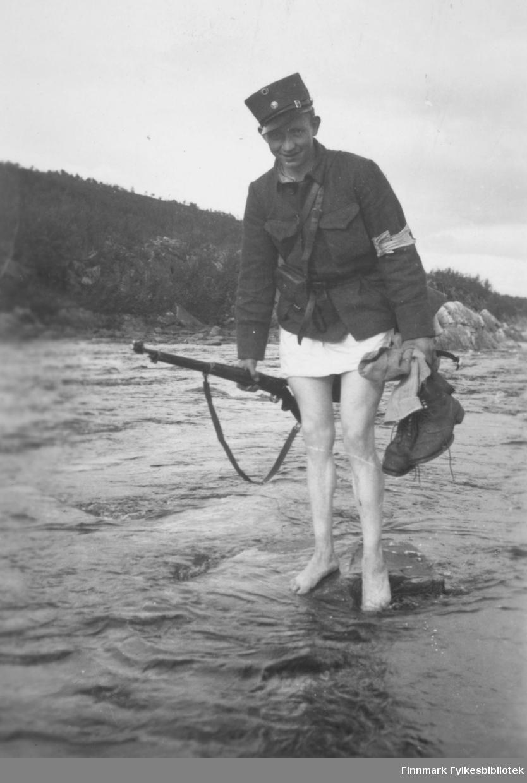 """Soldat med nakne hvite bein og gevær i ferd med å krysse ei elv. Innskrift i album: """"Korpen"""" vasser over elven. 1938."""