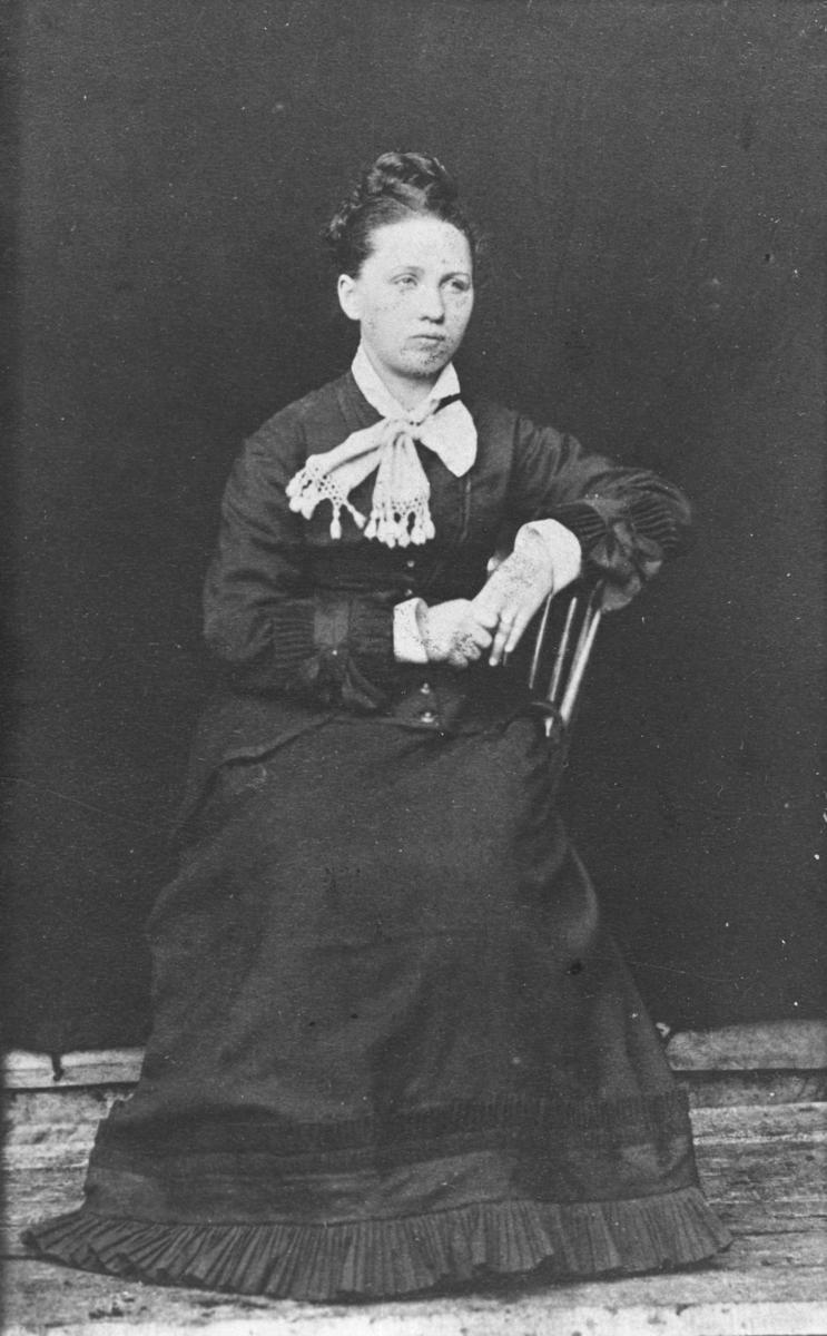 Portrett av en kvinne i mørk lang kjole, skjorte og en stor hvit sløyfe rund halsen. Hun sitter på en stol og lener med venstre armen på ryggstøen. Dette visitkortet har døde kanter (P.O.Næss?) og det er tatt tidlig på 1860 årene, kanskje tidligere