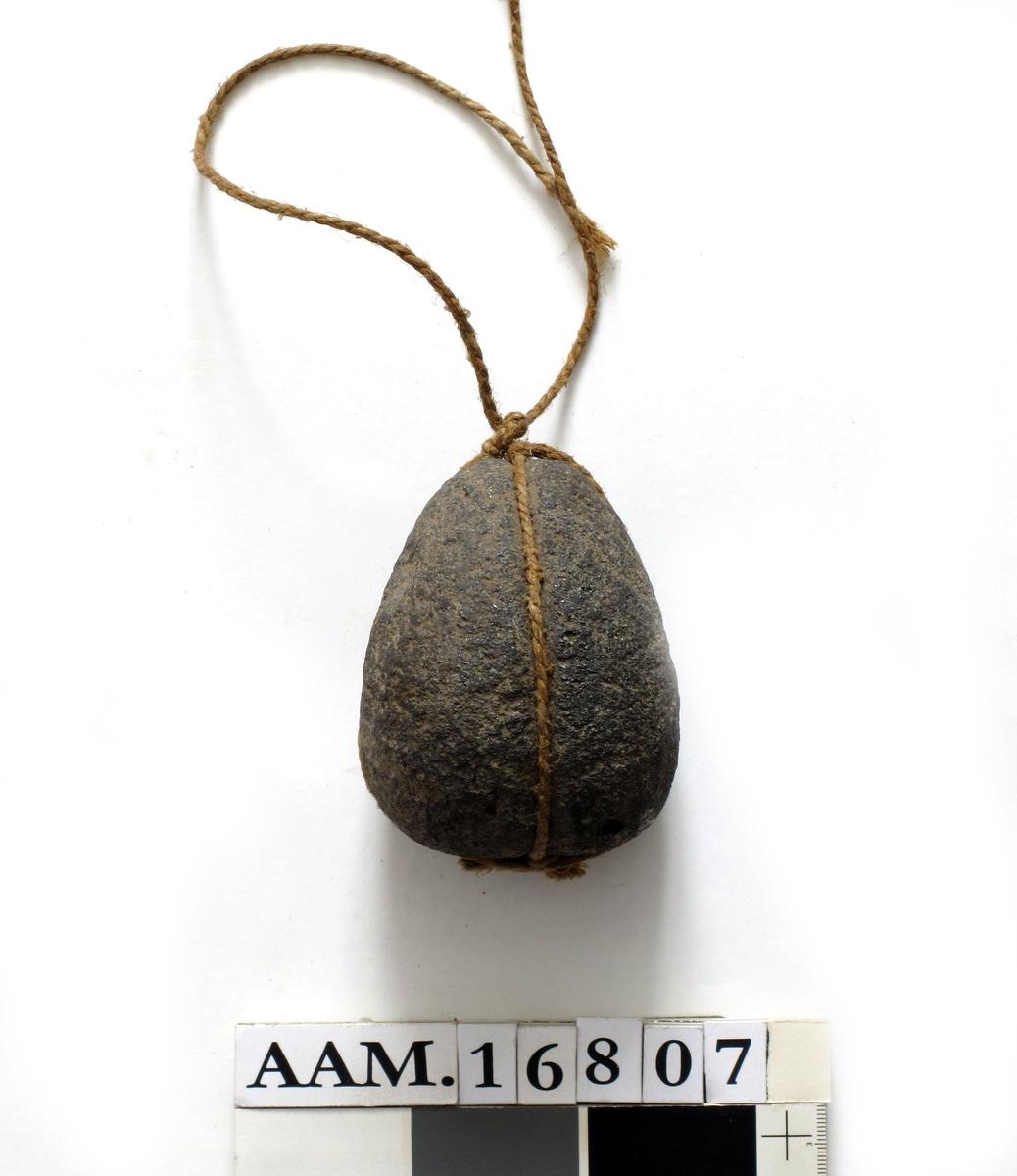 Fiskesøkke av stein. Dråpeformet, med to omgående riller,  som skjærer hverandre i kors i bunnen  og den spissere topp. Ingen tverr riller.  Vårt søkke er ombundet i rillene med brun hyssing.