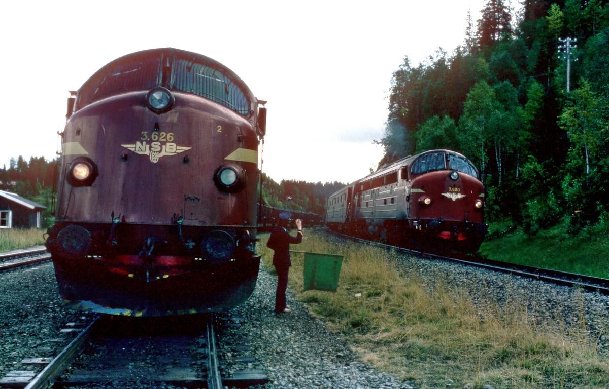 """Togekspeditør viser signal """"Passer"""" til sørgående dagtog 452 på Storforshei, mens et lastet malmtog fra Rana Gruber venter."""