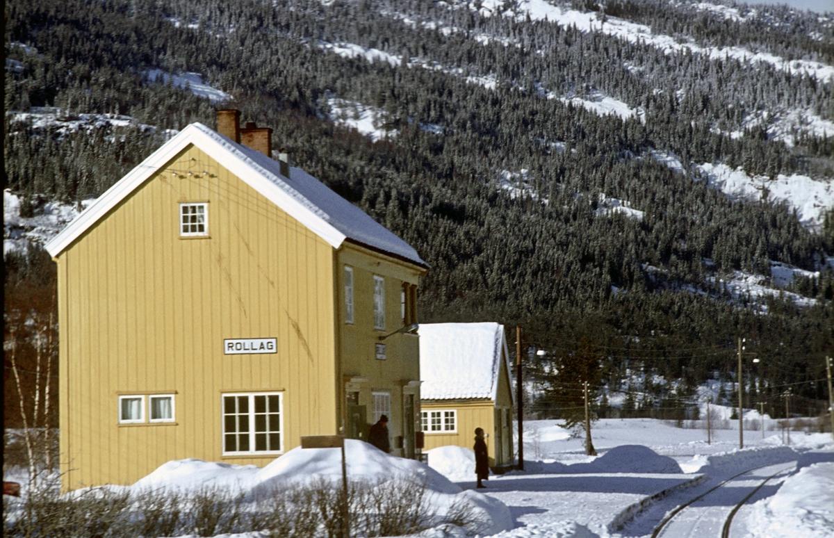 Rollag stasjon, Numedalsbanen. Numedal. Stasjonsbygning og uthus sett fra tog retning Rødberg. En reisende venter på toget.