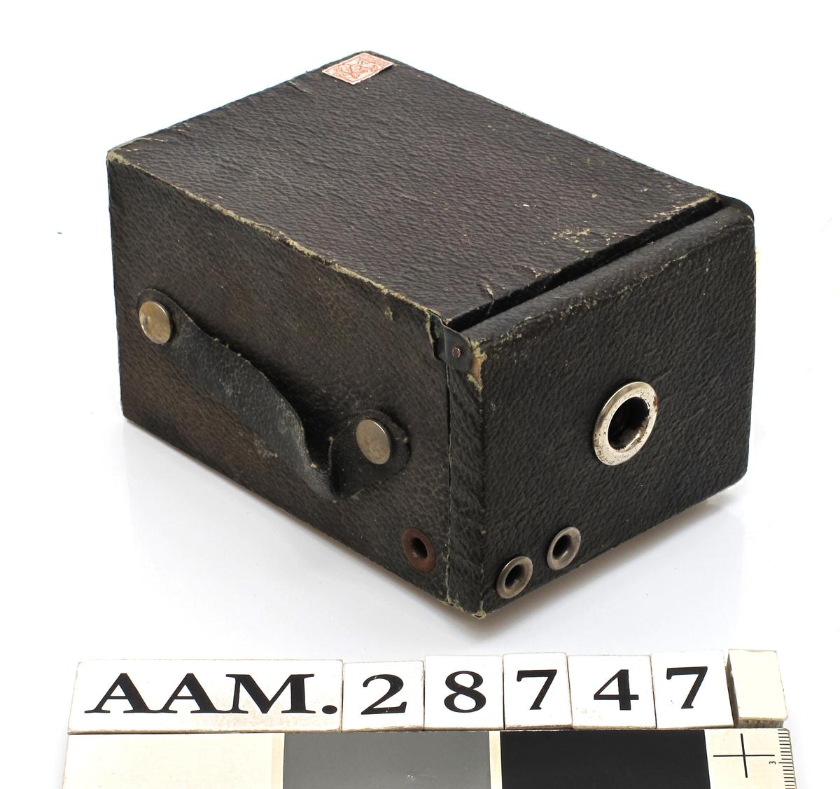 Utseende som et fotoapparat, et kassapparat, vanlig kameratype i 1950-årene. Når en trykker på utløseren spretter det ut en stor larve festet på en fjær.