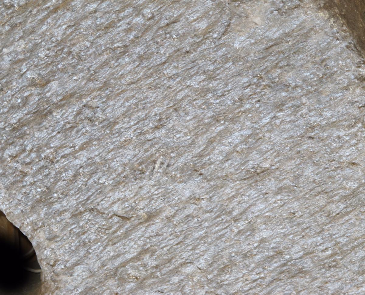 En kvernstein, riflet regelmessig overflate. Sirkelrundt hull, plassert midt i steinen.
