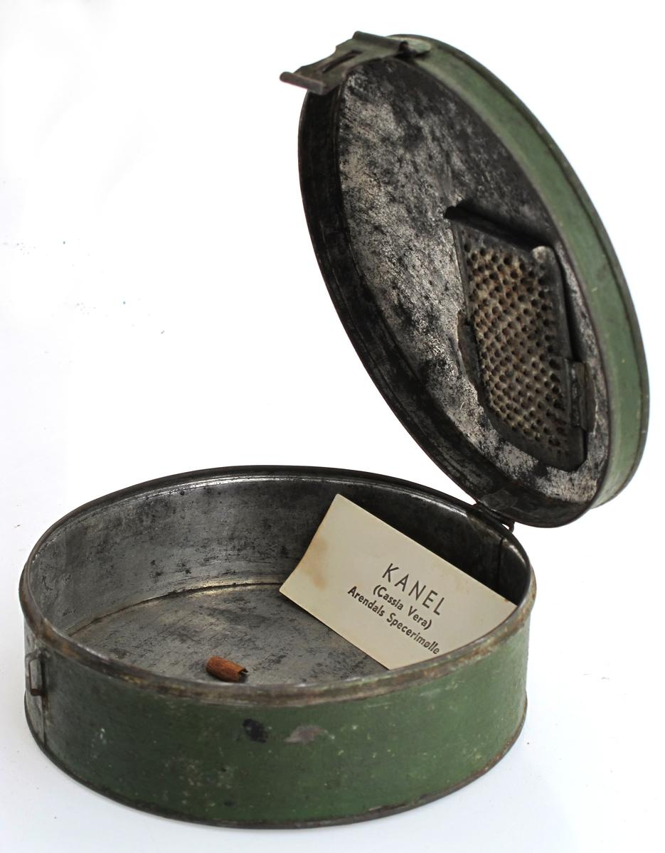 Krydderboks med rasp. Av jernblikk, grønnmalt.   Rund  boks med en rund stål trådhank på et svakt rundet lokk. Lokket festet til boksen med  et hengsel, på den annen side lås. Umalt innvendig. På  innsiden  av lokket er festet en rektangulær svakt buet rasp. Nedi  ligger  små hele kanelstykker og et stykke papir med trykte  bokstaver:   Kanel (Cassia Vera) Arendals Specerimølle.
