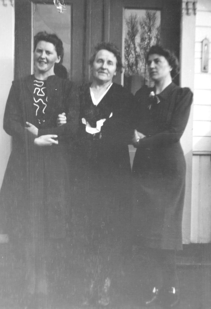 Tre damer står foran en utgangsdør. Damene har mørke pene kjoler på seg.  Døren er dobbel med glass.