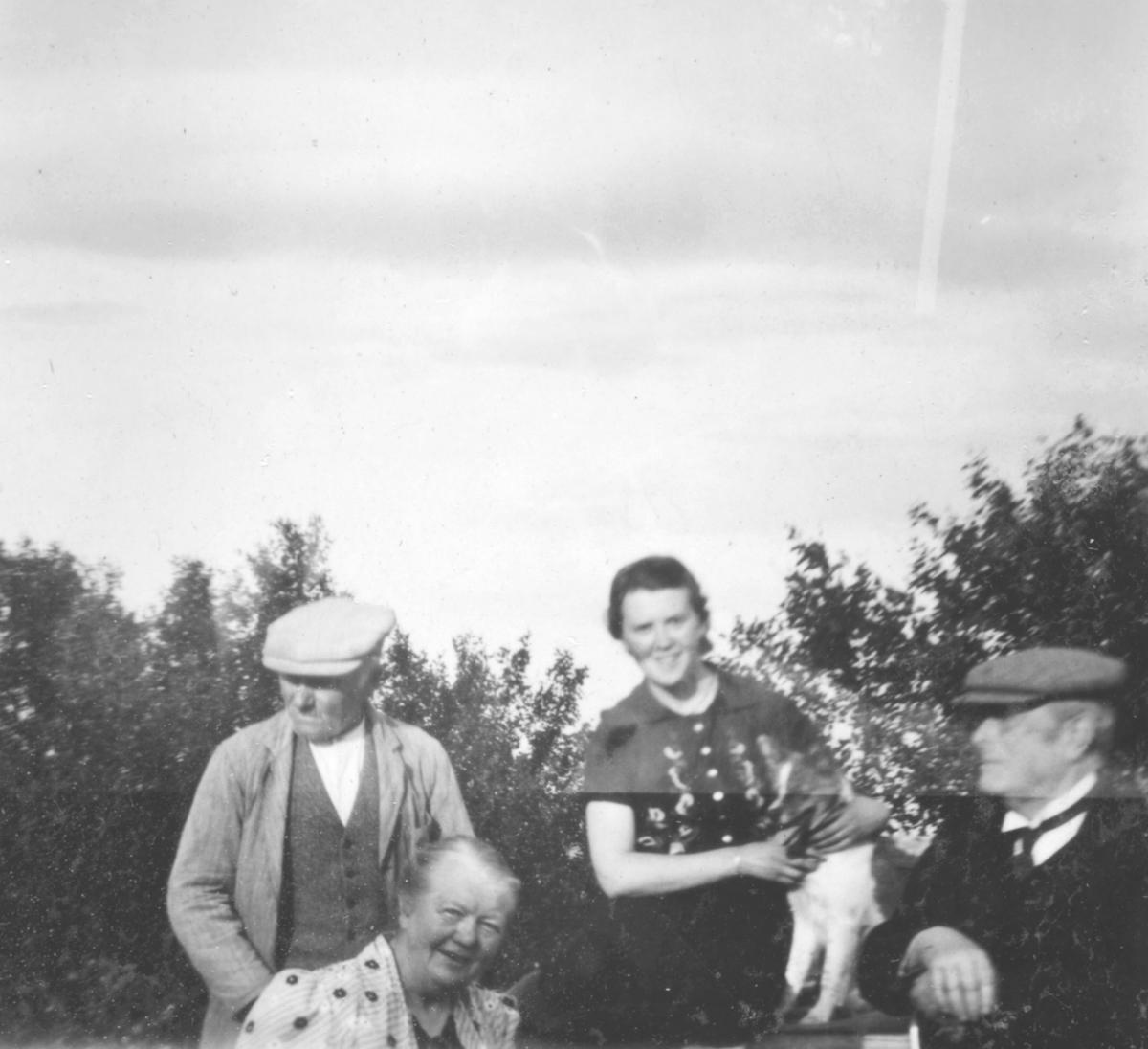 En dame står med en hund foran seg. Hunden ligger på en kasse eller lign. To menn på hver side og en dame til venstre foran. Antagelig Karoline Ohlsen. Bak er det trær.