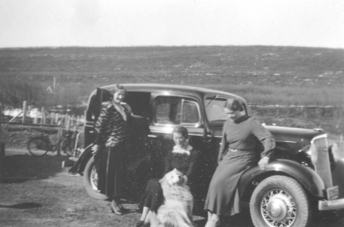 Bilde av noen damer som står ved siden av en bil, en Chevrolet 1934 mod.
