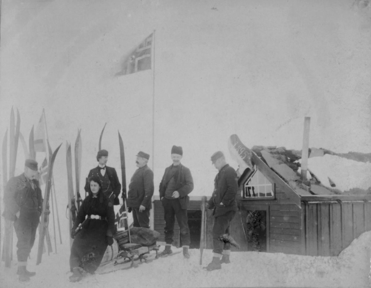 Menn og damer utenfor en hytte. En kjelke med en tønne og sekker. Foran kjelken ligger en mann. Ski står stablet i sneen.