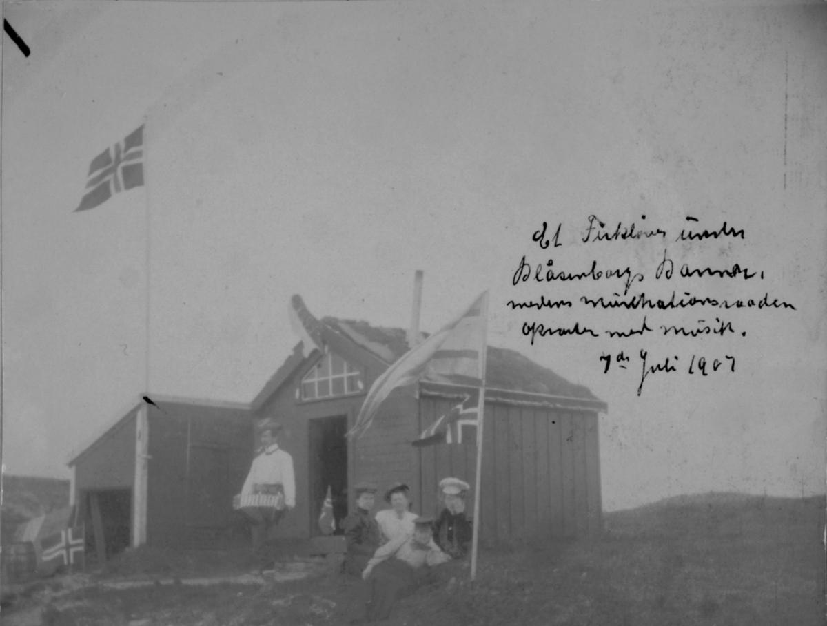 Et firkløver under Blåsenborgs banner, mens musikanten åpner med musikk. 7. juli 1907.
