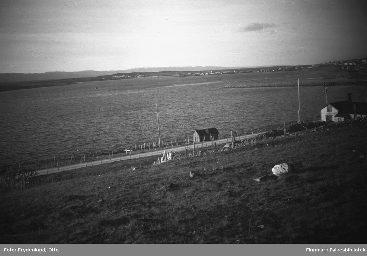 Langt øst i Vardøveien i Vadsø. Fotografen har stått på en liten høyde over veien, og vi ser et bolighus med tilhørende uthus