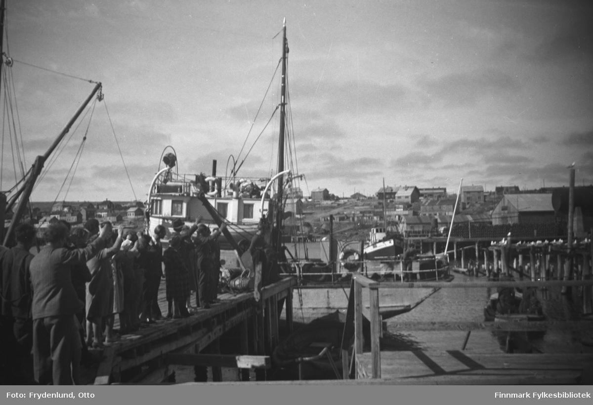 Folk står på dampskipskaia og vinker etter en liten motorbåt som legger fra kai. Mest sannsynlig er dette sjaluppen som hadde fraktet Kong Haakon VII fra jageren Stord og inn til kaia i Vadsø