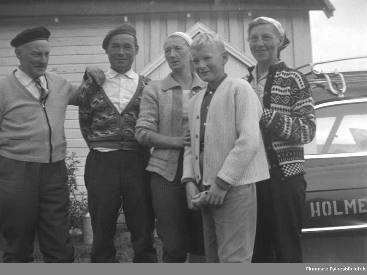 Kjøpmann Holm og kona kom på besøk til Mikkelsnes, ca. 1962-1965. Fra venstre: Kjøpmann Holm, Mikkel Smuk, Marine Smuk, Sture Olsen Lie, fru Holm. Antakelig har Holms kommet med bil, for gruppebildet er tatt like ved en personbil med påtrykte bokstaver 'HOLME...'