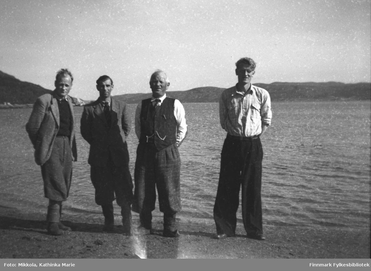Besøk fra Finnmark jordsalgskontor, bildet er tatt i fjæra ved Mikkelsnes. Fra venstre: To menn fra jordsalgskonoret, Aksel Konrad Mikkola med vest, urkjede og kommager, Mikkel Mikkola. Bildet er tatt ved samme anledning som 05007-319