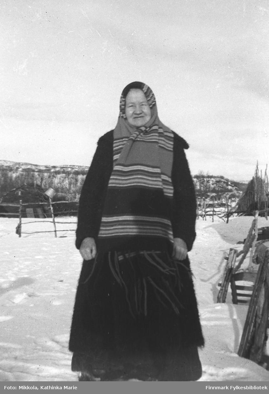 Portrett av en ukjent, eldre kvinne. I bakgrunnen en torvgamme, og på høyre side en stor stabel staurer - kanskje vedlager