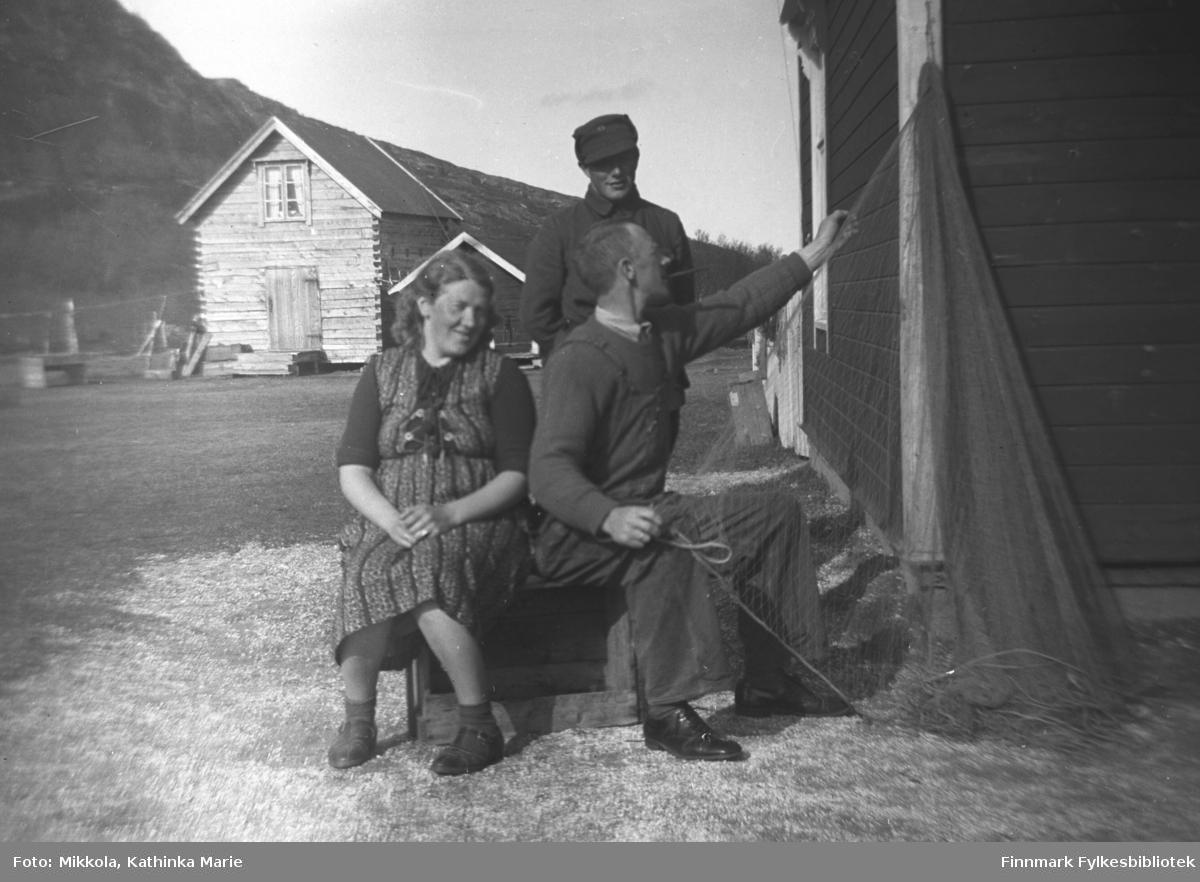 Per Olsen bøter og reier garn utendørs på Mikkelsnes. Til venstre Synnøve Olsen, bak står Torleif Valla i uniform. I bakgrunnen ser vi melkebua på gården