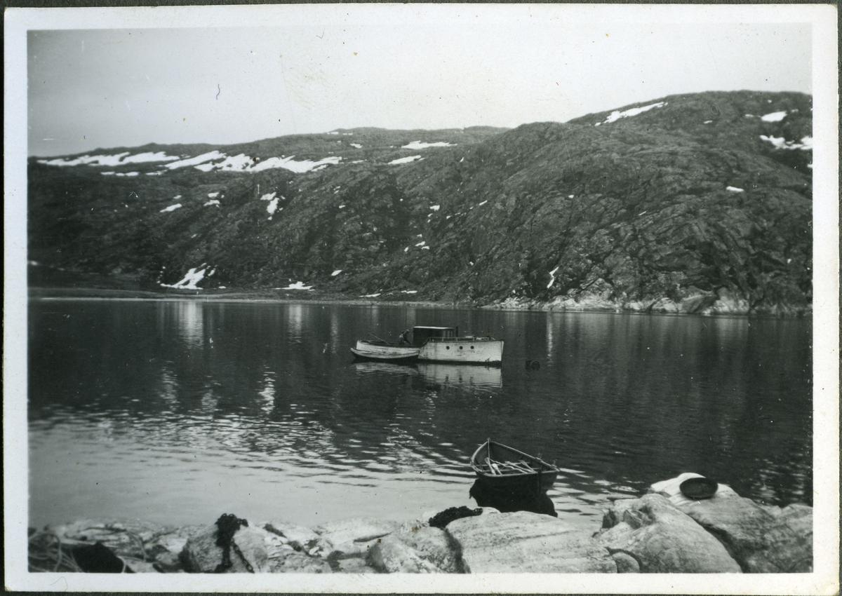 """""""Kaiser"""" er ankret i Sommervika. To menn står i den. En robåt med årene i seg ligger nærmere land. I området kan man se fjærasteiner og fjell. I fjæra kan man se en haug med kjetting (t.v.). Båten kan ha hørt til skiferbruddet i Friarfjord, men dette er noe usikkert. Bildet er tatt annsynligvis en gang på 50-tallet, eller begynnelsenav 60- tallet."""