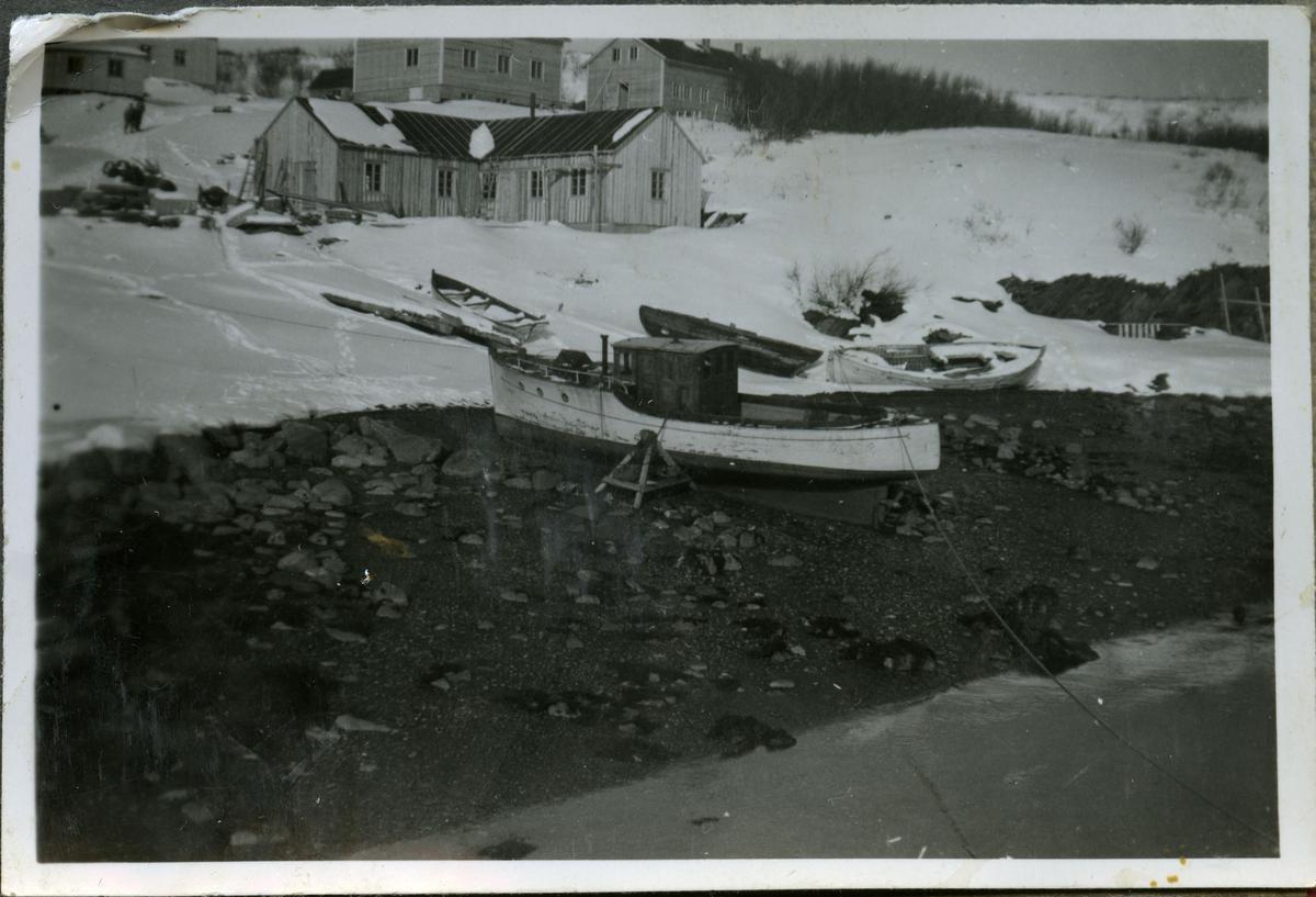 Skiferbruddet i Friarfjord opererte med egen båt til transport. Her ser man en båt som er dregt på land. Flere små robåter ligger i snøen ikke langt unna. Den nærmeste bygningen er smien på skiferbruddet. Rett bak den er kantinen og ved siden av kantinen kan man se brakken arbeiderne bodde i. I øverste venstre hjørne kan man se badstuen og bak den ser man et bygg som trolig har fungert som post-og kontorbygg.
